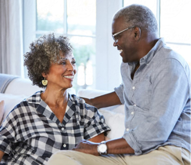 Older couple sitting on couch smiling at each other